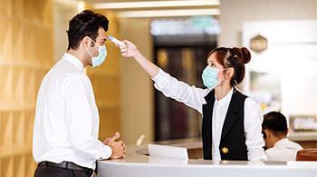 Woman at counter taking mans temperature