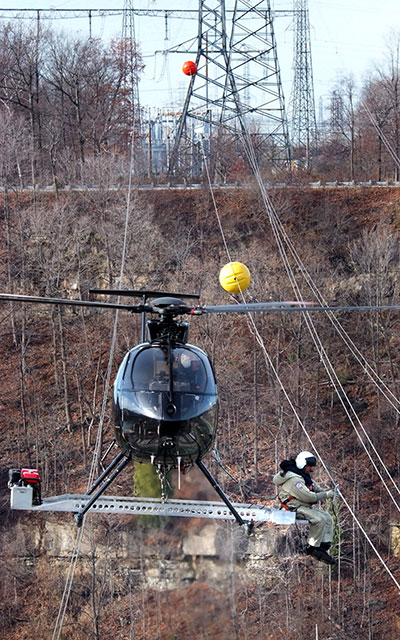 Power line marker being installed by helicopter